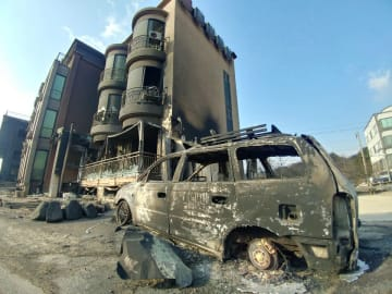山火事が延焼して焼けた建物と車両=5日、韓国北東部・江原道(聯合=共同)