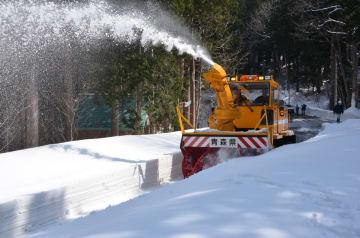道路に積もった雪をかき込みながら進む除雪車=4日、むつ市