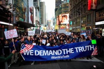 4日、米ニューヨークで、モラー特別検察官の捜査報告書の全面開示を求めて行進する人々(ロイター=共同)