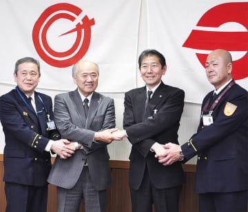 握手を交わす両市町の首長と消防長
