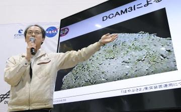 探査機はやぶさ2が、小惑星りゅうぐうの表面に大きな金属弾を撃ち込む世界初の実験に成功したと発表し、地下の岩石などが噴出する様子を捉えた画像を示しながら説明するJAXAの津田雄一准教授=5日午後4時33分、相模原市