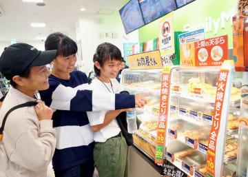 沖縄ファミリーマートで限定販売されている上間天ぷらを選ぶ来店者=4日、那覇市国際通りのレグザリウボウ店