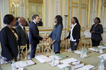 5日、フランス大統領府で、ルワンダ大虐殺の生存者の団体代表者らと面会するマクロン大統領(左から3人目)=パリ(ロイター=共同)