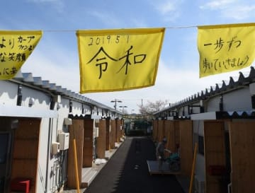 新元号「令和」の文字が書かれた布と仮設住宅=倉敷市・真備総合公園