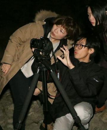 アマチュア写真家の野上香織さん(左)の指導で星空と原尻の滝の撮影に挑む留学生ら=豊後大野市緒方町