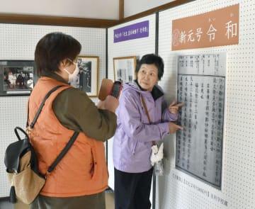 万葉集の特別展示を始めた足利学校で、「令和」の典拠部分の拡大パネルと写真に納まる来場者=6日午前、栃木県足利市