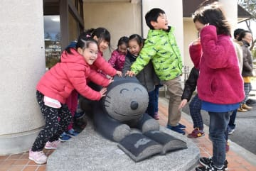 三戸町立図書館玄関前に設置された「絵本を読むねこ」の石像に触れる子どもたち