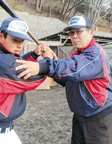 選手に打撃を指導する佐々木さん(右)=4日、仙台市太白区の東北工大野球場