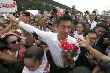 タイの首都バンコクの警察署に到着し、支持者に囲まれる革新政党「新未来党」のタナトーン党首=6日(AP=共同)