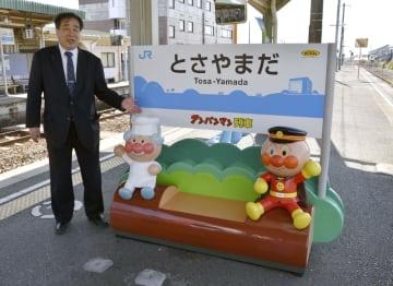 JR土佐山田駅に設置されたアンパンマン(右)、ジャムおじさんと座れるベンチ。左は中谷茂駅長=高知県香美市
