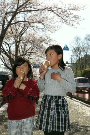「冷たさがちょうどいい」。満開の桜の下でソフトクリームを食べる姉妹=6日、豊後大野市清川町