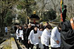 最澄像が納められた厨子を引いて金剛寺の参道を歩く檀家ら=三田市上本庄