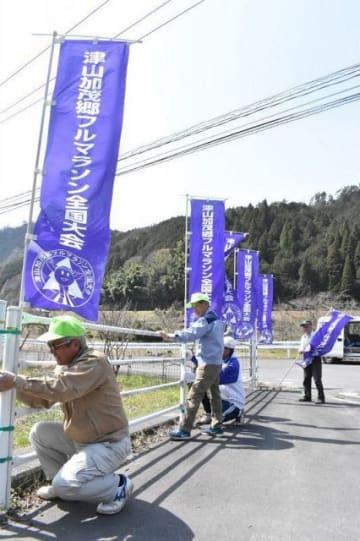 コース沿道にのぼり旗を取り付ける住民ら=津山市加茂町知和