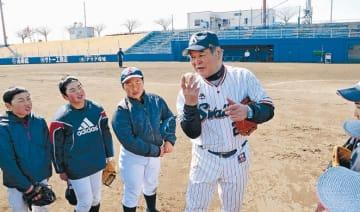 子どもたちにボールの握り方を教える八重樫さん