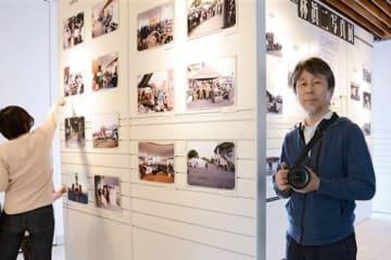写真展会場で「町の移ろいから復興の歩みを感じてほしい」と話す林眞二さん(右)=益城町