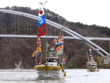 気仙沼大島大橋の開通を祝い、大漁旗を掲げて橋の下を航行する漁船団=7日、宮城県気仙沼市