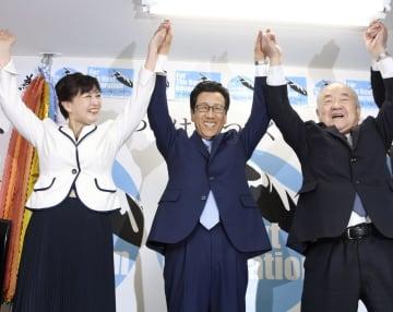 札幌市長選で再選を確実にし、万歳する秋元克広氏(中央)=7日夜、札幌市中央区