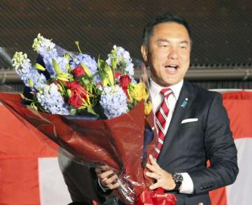 三重県知事選で3選を確実にし、花束を手にする鈴木英敬氏=7日夜、津市