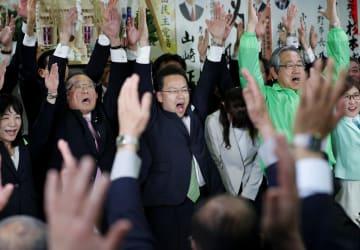 福井県知事選で初当選を確実にし、万歳する杉本達治氏(中央)=7日夜、福井市