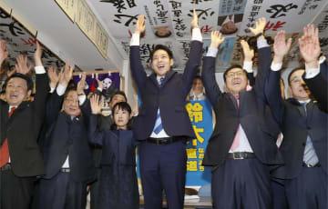 北海道知事選で当選を確実にし、万歳する鈴木直道氏(右から3人目)=7日夜、札幌市中央区