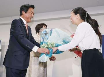 福岡県知事選で3選を確実にし、花束を受け取る小川洋氏(左)=7日夜、福岡市