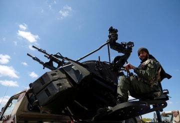7日、リビアのベンガジからトリポリへ向け進軍する「リビア国民軍」のメンバー(ロイター=共同)