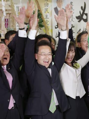 福井県知事選で当選確実となり、万歳する杉本達治氏=4月7日夜、福井県福井市