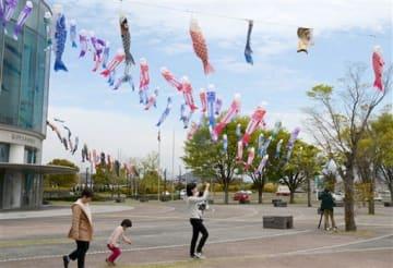 グランメッセ熊本で春風を受けて泳ぐこいのぼり=益城町