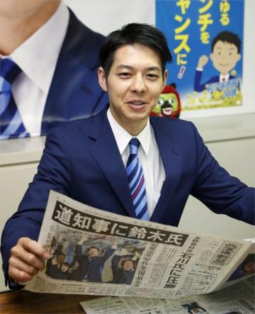 北海道知事選から一夜明け、当選を伝える新聞を手に取材に応じる鈴木直道氏=8日午前、札幌市中央区