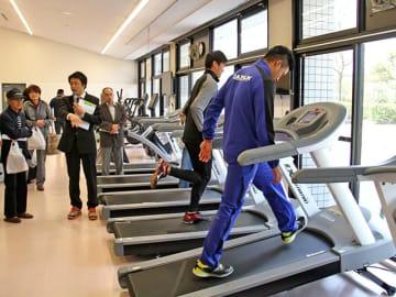 一新されたトレーニングマシンを見学する関係者ら=恵那市長島町、まきがね公園体育館