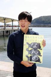 ポスターを手に、意気込みを語る河合健さん=洲本市海岸通1