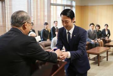 中村知事(左)から認定証とバッジを受け取る長崎コンシェルジュの合格者=長崎県庁