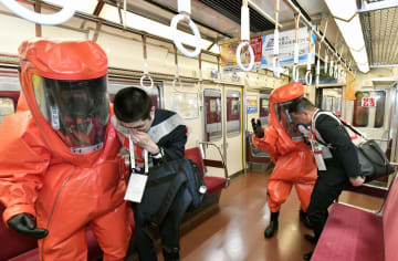 G20首脳会合に備え行われたテロ対策訓練で、異臭が発生した列車内から連れ出される乗客役=9日午後、大阪市の近鉄大阪上本町駅