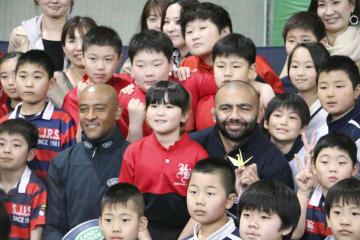 子どもたちと記念撮影するラグビー日本代表のリーチ・マイケル主将(中央右)と元オーストラリア代表のジョージ・グレーガン氏=9日午後、札幌市
