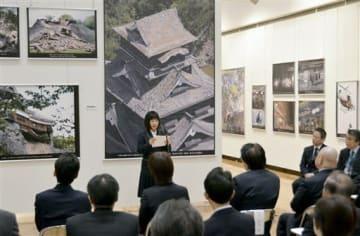 「熊本地震・東日本大震災報告写真展」の開幕式典で、ボランティア体験の作文を朗読する尚絅高3年の井手麻那美さん(奥中央)=熊本市中央区