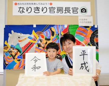 「令和」を持って記念撮影する来館者の杉田朱理君(左)と、企画した司書の濱田幸男さん=唐津市新興町の同市近代図書館