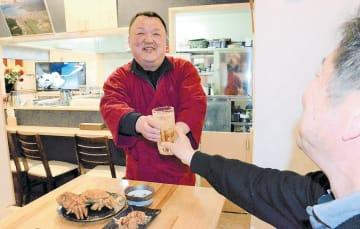 笑顔で客に酒を手渡す三浦さん