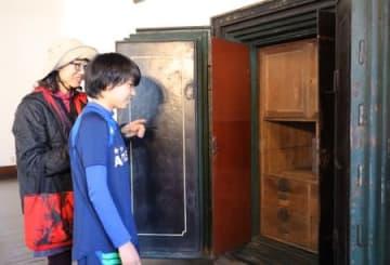 旧直江津銀行時代に使われていた金庫をのぞき込む親子連れ=上越市