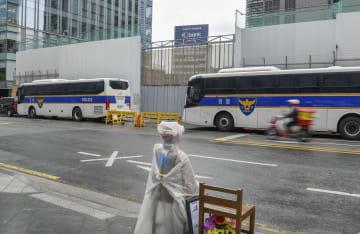 塀で覆われた建て替えが計画されているソウルの日本大使館の敷地(奥)。手前に従軍慰安婦問題を象徴する少女像が設置されている=10日(共同)