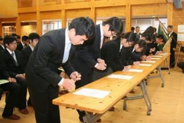 入学宣誓書に署名する新入生たち
