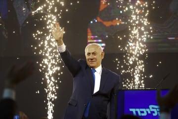 右手を上げて支持者に応えるイスラエルのネタニヤフ首相=10日、テルアビブ(AP=共同)