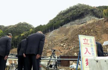 山崩れの発生から1年となり、現場に黙とうをささげる市職員ら=11日午前、大分県中津市耶馬渓町