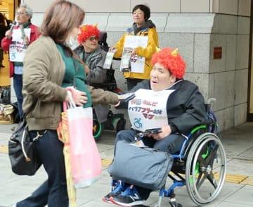 バリアフリーマップを配布する山下さん(左)=10日、大阪市中央区の高島屋大阪店前