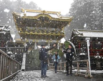 雪が降る中、陽明門の前で記念撮影する観光客ら=10日午前9時45分、日光市山内