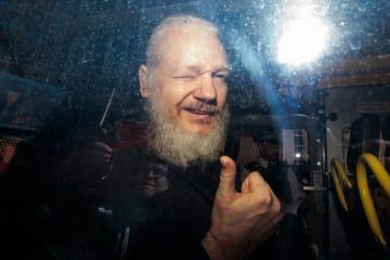 11日、英ロンドンで、警察の護送車の中からメディアに向かって指を立てるアサンジ容疑者(ゲッティ=共同)