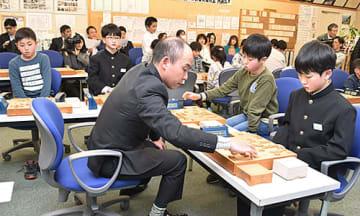 熊坂学五段(手前左)から対局指導を受ける1期生たち=天童市・天童将棋交流室