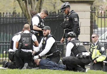 ホワイトハウス前で男がジャケットに火を付け、駆け付けた警官ら=12日、ワシントン(ロイター=共同)
