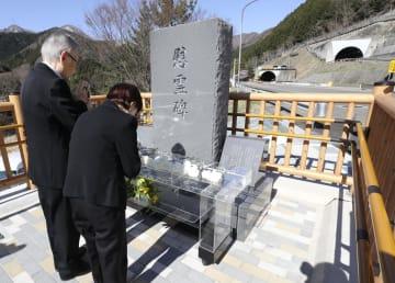 笹子トンネル近くに建てられた慰霊碑に手を合わせる天井板崩落事故の遺族ら=13日午前、山梨県大月市(代表撮影)