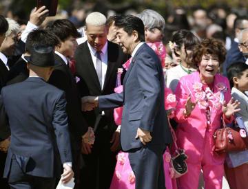 「桜を見る会」で招待客と握手を交わす安倍首相(中央)=13日午前、東京・新宿御苑