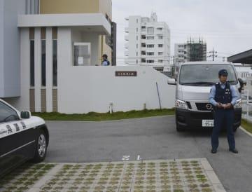 男女2人が死亡した沖縄県北谷町桑江のアパートを警戒する沖縄県警の警察官=13日午前